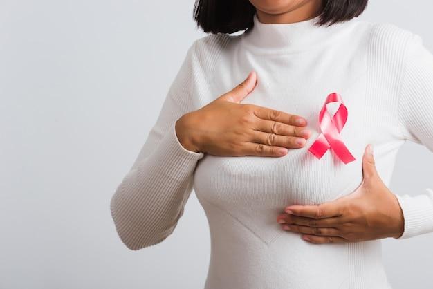 Vrouw ze heeft een roze lint voor borstkanker op de borst, ze houdt de borst met de hand vast