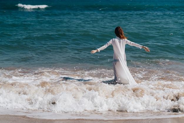 Vrouw zee oceaan mooie jurk lopen aard