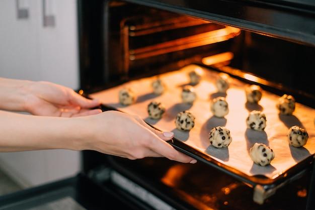 Vrouw zet bakplaat met rauwe koekjes in de oven, close-up