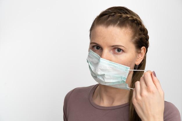 Vrouw zet een beschermend masker op haar mond om zichzelf te beschermen tegen virale ziekten en bacteriën.