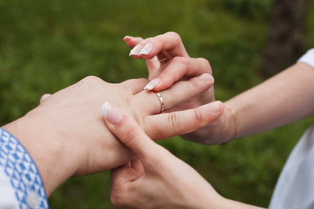 Vrouw zet een trouwring om een man.