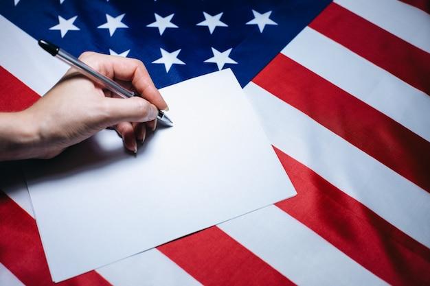 Vrouw zet een vinkje op het papier om te stemmen. politieke veranderingen in het land. kopieer ruimte plaats. verkiezingen in de vs. amerikaanse vlag. mensen stemmen op de stemming.