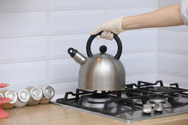 Vrouw zet een waterkoker op de keuken in handschoenen aan gasfornuis. kookfluitketel in de hand. selectieve aandacht