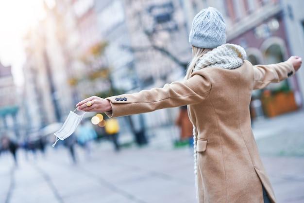Vrouw zet gezichtsmasker af in de stad