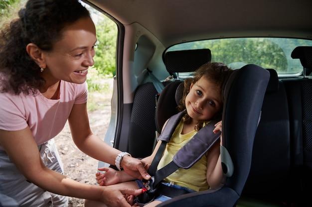Vrouw zet haar dochter in het autostoeltje en maakt het kind vast met een veiligheidsgordel. veiligheid van reizen in een auto met kinderen