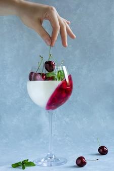 Vrouw zet kers in wijnglas met dessert. panna cotta met bessen in glas op grijs.