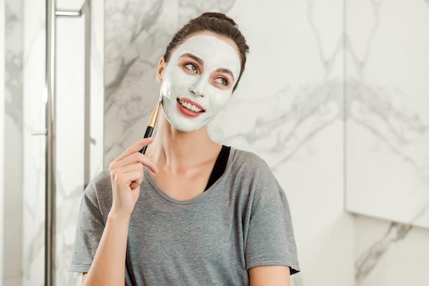 Vrouw zet klei masker op haar gezicht en lachend in de badkamer