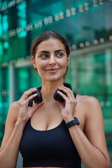 Vrouw zet koptelefoon af om met vriend te praten loopt buiten heeft fitnesstraining verbrande calorieën na het eten van calorierijk voedsel ziet er voldaan uit na het sporten. welzijn en sport
