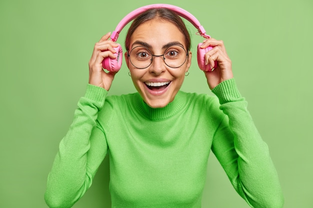 Vrouw zet koptelefoon op glimlacht vrolijk luistert audiotrack is blij humeur draagt ronde bril en coltrui op groen