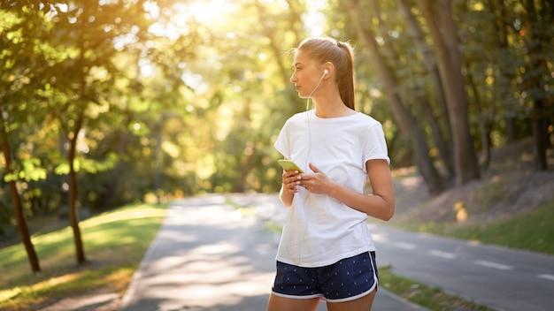 Vrouw zet oortelefoons op om naar muziek te luisteren voordat ze in het zomerpark gaat joggen