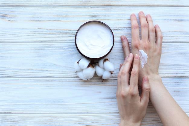Vrouw zet op handen crème, handverzorging, bovenaanzicht
