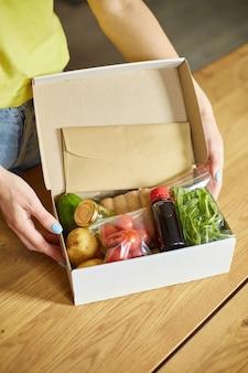 Vrouw zet op tafel een maaltijdbox maaltijdpakket met verse ingrediënten bestellen bij een maaltijdpakketbedrijf, bezorgd, thuis kokend.