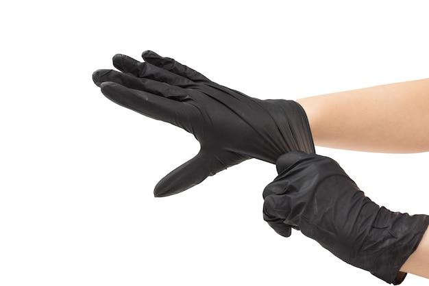 Vrouw zet op zwarte rubberen handschoenen geïsoleerd op wit