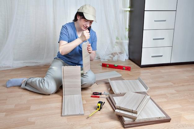 Vrouw zet planklade vast, met behulp van lijm, montage van houten meubels.