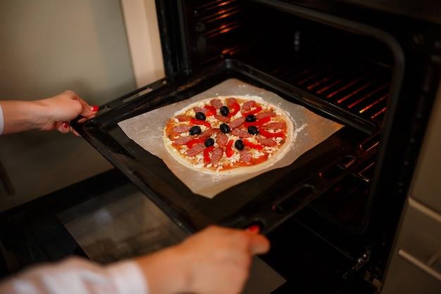 Vrouw zet rauwe pizza met ingrediënten en tomaat, kruiden, worst