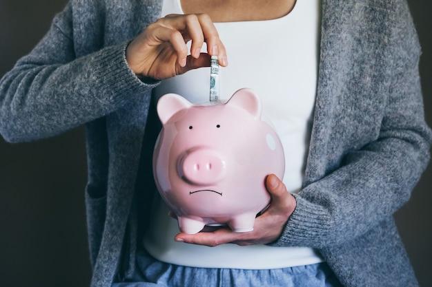 Vrouw zet rekening in droevig spaarvarken vrouw spaart geld voor huishoudelijke betalingen bankrekeningen