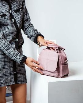 Vrouw zet roze lederen tas op de witte standaard