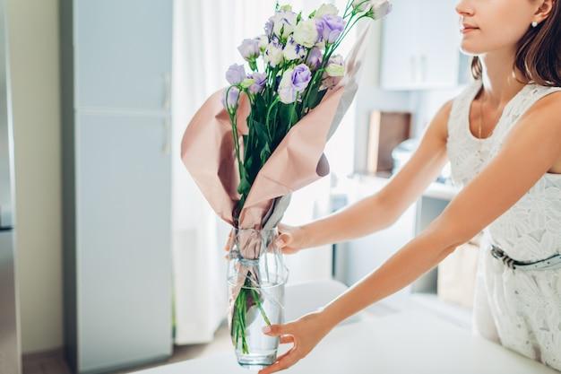 Vrouw zet vaas met bloemen. huisvrouw die gezelligheid in keuken behandelen. modern keukenontwerp