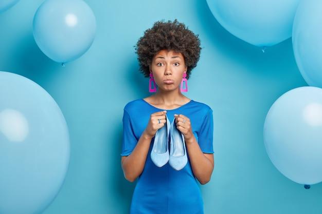 Vrouw ziet er droevig uit met portemonnees lippen houdt blauwe schoenen om te passen jurk kiest outfit om te dragen voor speciale gelegenheid geïsoleerd op blauw