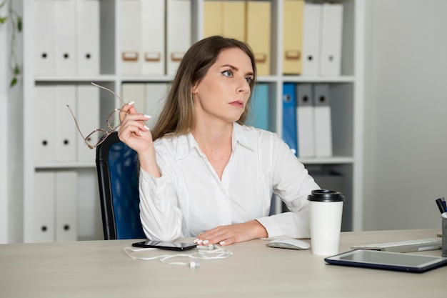 Vrouw ziet er moe uit op het werk vanwege haar tijd aan de telefoon