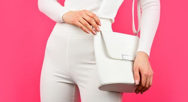 Vrouw ziet er stijlvol uit. modieuze vrouw met trendy leren tas. vrouwelijke geheimen. hele wereld in één tas. handtassen en accessoires winkel. meisje presenteert koppeling roze achtergrond.
