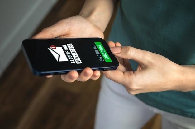 Vrouw zingt de nieuwsbrief op het scherm van de mobiele telefoon binnenshuis, e-mailmarketingconcept achtergrondfoto