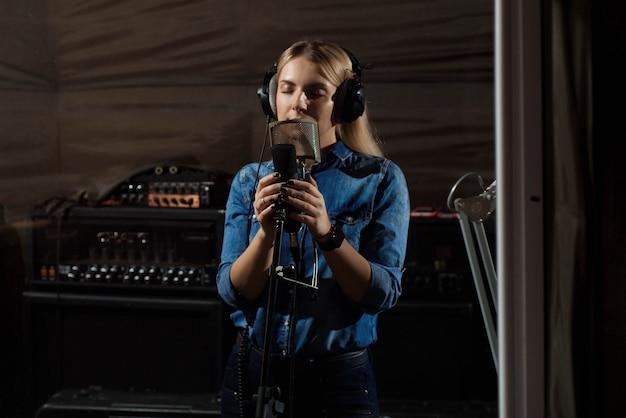 Vrouw zingt een lied met mobiele telefoon in opnamestudio.