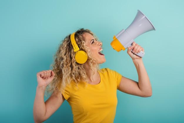 Vrouw zingt met luidspreker en luistert naar muziek met een vrolijke uitdrukking op de koptelefoon
