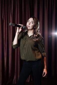 Vrouw zingt op het podium in de microfoon karaoke