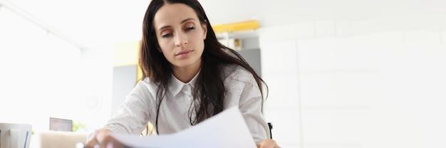 Vrouw zit aan bureau houdt document lees papieren brief voelt zich teleurgesteld geschokt door slecht nieuws