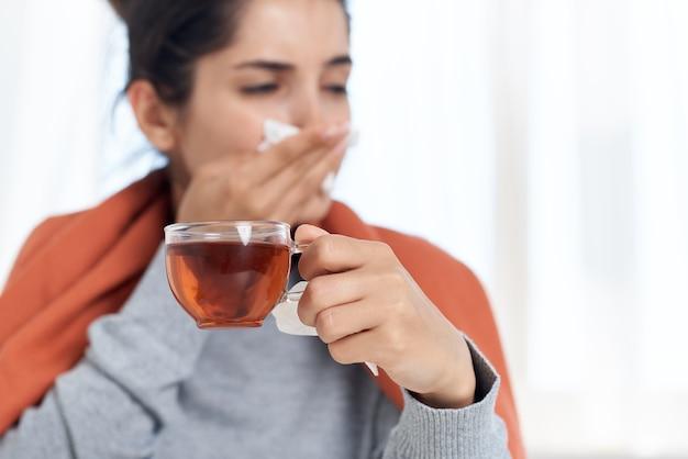 Vrouw zit aan een tafel met een deken op haar schouders en behandelt thuis een verkoudheid