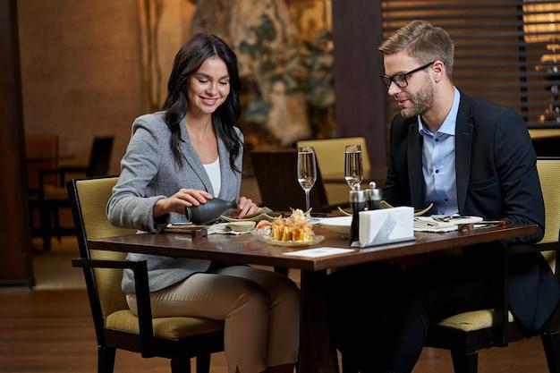 Vrouw zit aan gedekte tafel met veel eten terwijl ze de zwarte kan met saus omdraait in een klein wit kopje