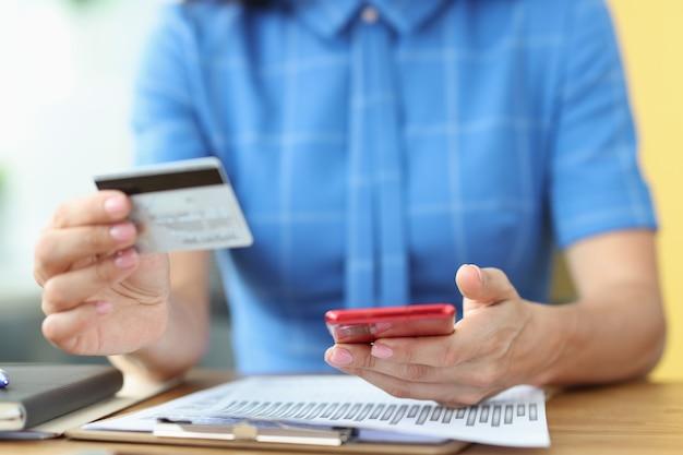 Vrouw zit aan tafel met documenten en houdt mobiele telefoon en creditcard in haar
