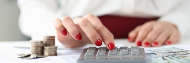 Vrouw zit aan tafel met geld en rekent op het succesvolle bedrijf van het rekenmachineconcept en
