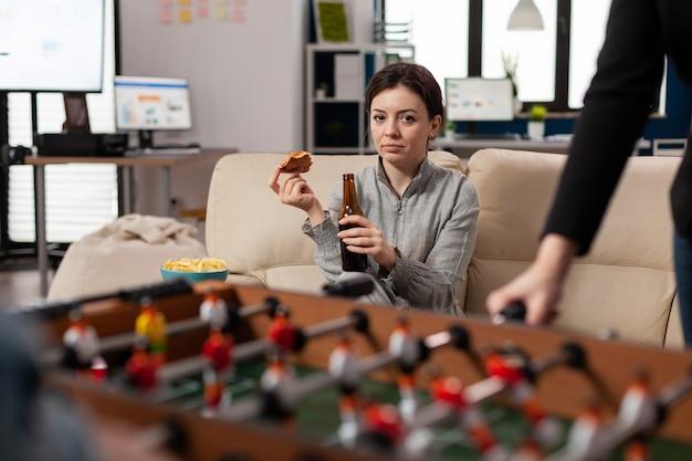 Vrouw zit aan tafelvoetbal op kantoor na het werk