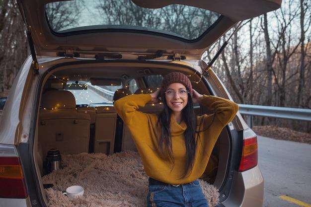 Vrouw zit achterin de kofferbak. klaarmaken om te gaan. jonge lachende vrouw zit in de open kofferbak van haar auto. herfst roadtrip. hipster paddenreizen, herfstvakantie