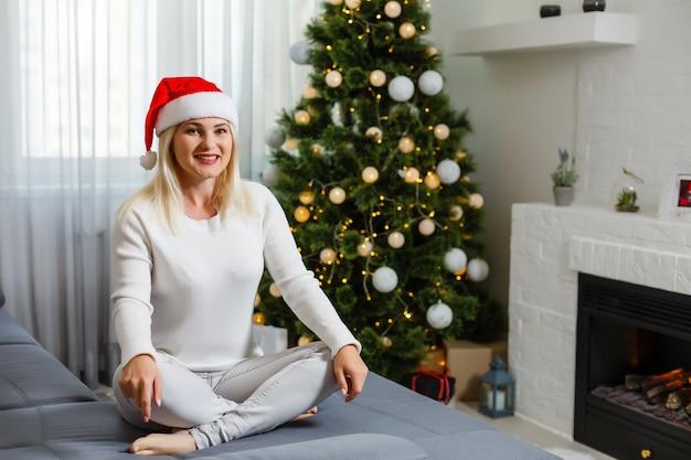 Vrouw zit alleen bij een kerstboom