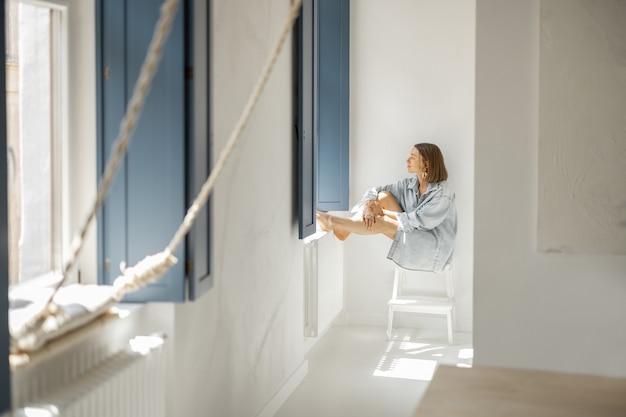 Vrouw zit alleen bij het raam thuis