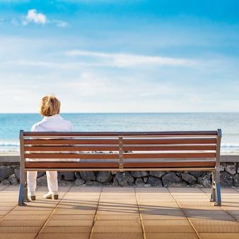 Vrouw zit alleen in een bankje, kijkend naar de zee