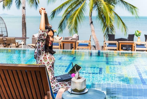 Vrouw zit bij het zwembad met uitzicht op de oceaan die op een laptop werkt