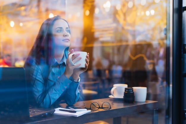 Vrouw zit buiten het raam koffie te drinken