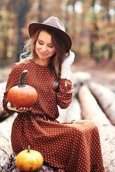 Vrouw zit en houdt wat pompoenen vast