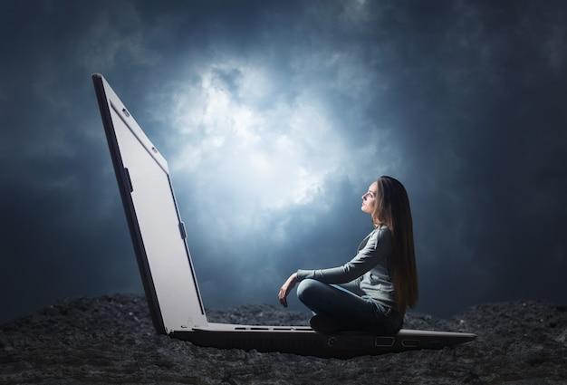 Vrouw zit en kijkt naar het scherm op een grote laptop