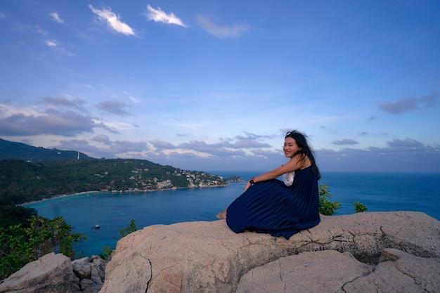 Vrouw zit en ontspant op de rots bij het uitkijkpunt van het zeegezicht, john-suwan-gezichtspunt op de koh tao-eilanden, plaats voor toeristische bestemming in suratthani, thailand
