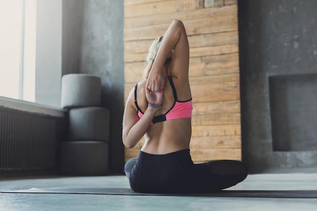Vrouw zit en strek handen achter rug bij yogales, gomukhasana-oefening. achteraanzicht van flexibele yogi meisje beoefenen van yoga of pilates, zittend in koe gezicht pose