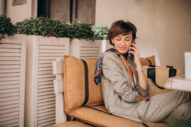 Vrouw zit in café en gebruikt telefoon