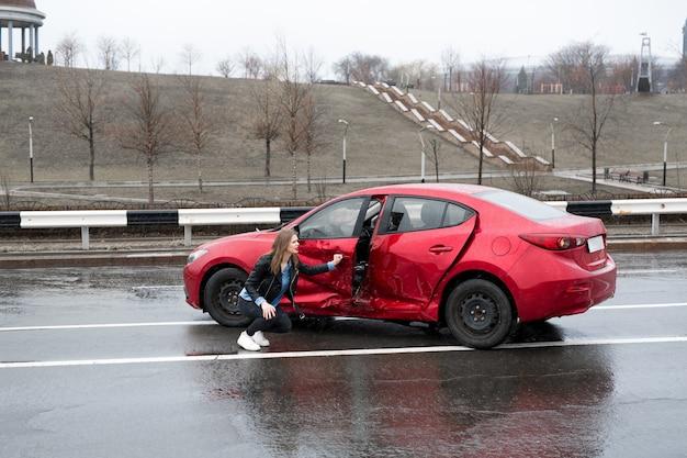 Vrouw zit in de buurt van een kapotte auto na een ongeval. roep om hulp. autoverzekering