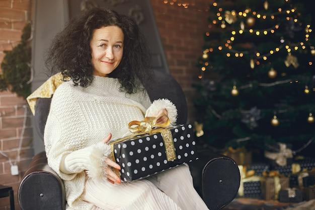 Vrouw zit in de buurt van open haard. dame in een witte trui. brunette in een kerstconcept.