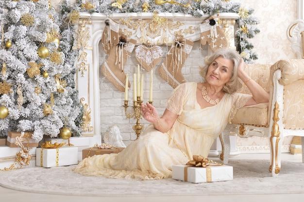 Vrouw zit in de buurt van stoel met geschenkdoos in kamer versierd met kerstmis