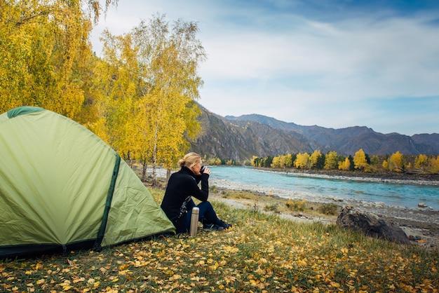Vrouw zit in de buurt van toeristische tent en drinkt hete thee